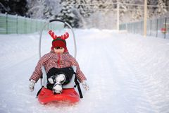 Adorable child girl in horned hat sled in snow Stock Images