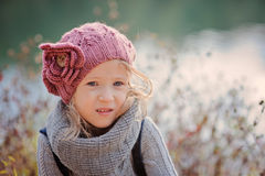 Adorable child girl in pink knitted hat and grey sweater close up portrait Stock Image