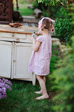 Adorable child girl in pink plaid dress near vintage bureau holding secateurs Royalty Free Stock Photos