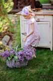 Adorable child girl in pink plaid dress near vintage bureau with lilacs in basket. In spring garden Stock Photo