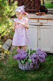 Adorable child girl in pink plaid dress with secateurs and basket of lilacs in spring garden Royalty Free Stock Photography