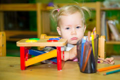 Adorable child girl playing with educational toys in nursery room. Kid in kindergarten in Montessori preschool class. Adorable child girl playing with royalty free stock images