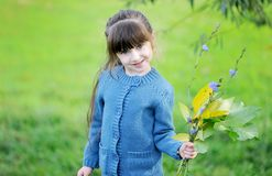 Adorable child girl poses outdoors with leaves Stock Photo
