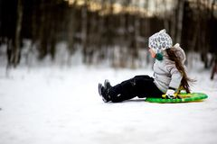 Adorable child girl sledding in snow on a saucer royalty free stock image