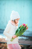 Adorable child girl with tulips bouquet on the walk in early spring Royalty Free Stock Photos