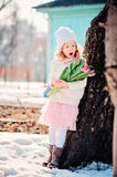 Adorable child girl with tulips bouquet on the walk in early spring Royalty Free Stock Image