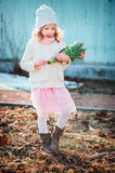 Adorable child girl with tulips bouquet on the walk in early spring Stock Image