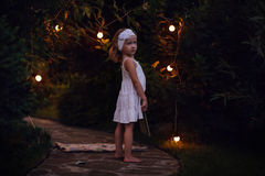 Adorable child girl in white dress with book in summer evening garden decorated with lights Stock Photos
