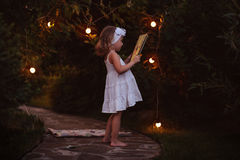 Adorable child girl in white dress with book in summer evening garden decorated with lights Stock Images