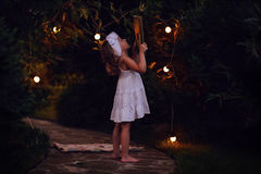 Adorable child girl in white dress holding book in summer evening garden decorated with lights Royalty Free Stock Image