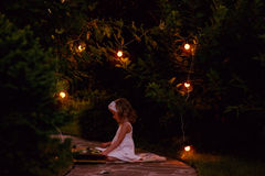 Adorable child girl in white dress reading book in summer evening garden decorated with lights Royalty Free Stock Photos