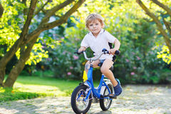 Adorable child having fun with riding his first bicycle Stock Images