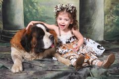 Adorable Child and Her Saint Bernard Puppy Dog Stock Photo