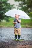 Adorable child holding an umbrella in a rain storm royalty free stock photography