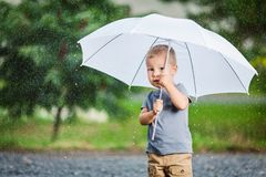 Adorable child holding an umbrella in a rain storm royalty free stock image