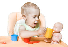 Adorable child independently feeding doll Stock Images