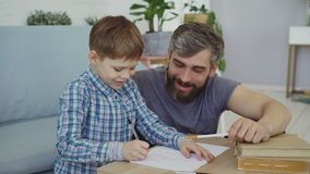 Adorable child junior school student is doing homework writing in exercise book with his father. Education, children stock footage