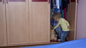 Adorable child kid hide best friend teddy bear into closet and close door stock video footage