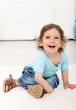 Adorable child laughing on the floor Royalty Free Stock Images