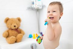 Adorable child learing how to brush his teeth. In the bathroom Royalty Free Stock Photos