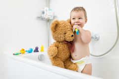 Adorable child learing how to brush his teeth. In the bathroom Royalty Free Stock Photography