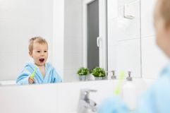 Adorable child learing how to brush his teeth. In the bathroom Stock Photo