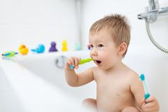 Adorable child learing how to brush his teeth. In the bathroom Stock Images