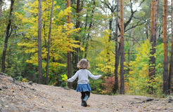 Adorable child, little curly toddler girl in blue dress playing in beautiful pine wood forest enjoying. Royalty Free Stock Images