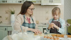 Adorable child and loving mother cooking in kitchen at home and talking
