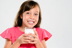 Adorable child with milk moustache. Cute young girl drinking and holding a glass of milk with a milk moustache stock image