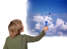 Adorable child painting a beautiful sky with a roller Stock Photography