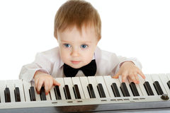 Adorable child playing electron piano. Over white Stock Images