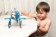 Adorable child playing with toy airplane. A cute little toddler boy plays with an retro style toy airplane on an Italian marble table by a window.  Child has Stock Photography