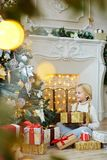 Christmas girl. Adorable child with present looking at decorated firtree while sitting by fireplace at home on xmas night Royalty Free Stock Image