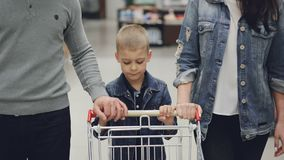 Adorable child is pushing shopping trolley inside food store, his loving parents are helping him. Children, young family. Adorable blond child is pushing stock video