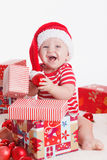 Adorable child in santa cap with stacks of present boxes around sitting on the floor. Isolated on white background Stock Photography