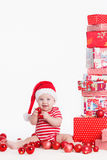 Adorable child in santa cap with stacks of present boxes around sitting on the floor. Isolated on white background Stock Photos