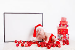 Adorable child in santa cap with stacks of present boxes around sitting on the floor. Isolated on white background Stock Images