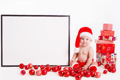 Adorable child in santa cap with stacks of present boxes around sitting on the floor. Isolated on white background Stock Photo