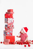 Adorable child in santa cap with stacks of present boxes around sitting on the floor. Isolated on white background Royalty Free Stock Photo
