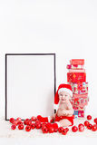 Adorable child in santa cap with stacks of present boxes around sitting on the floor. Isolated on white background Royalty Free Stock Image