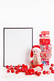 Adorable child in santa cap with stacks of present boxes around sitting on the floor. Isolated on white background Royalty Free Stock Photos