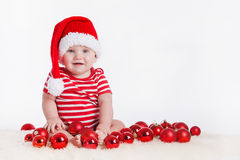 Adorable child in santa cap with stacks of present boxes around sitting on the floor. Isolated on white background Royalty Free Stock Images
