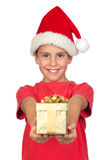 Adorable child with Santa Hat offering a gift Royalty Free Stock Photography