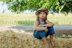 Adorable child sits on a haystack royalty free stock photography