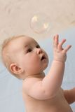Adorable child sitting and catching soap bubble Stock Photography