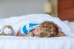 Adorable child sleeping and dreaming in his white bed with toy Stock Photos