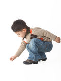 Adorable child in studio crouching Royalty Free Stock Photo