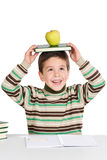 Adorable child studying with books and apple in th. E head a over white background Royalty Free Stock Photo