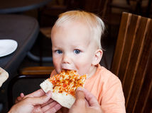Adorable child toddler boy eating pizza slice at a restaurant summertime. Looking at the camera. Surprise of eyes stock photos